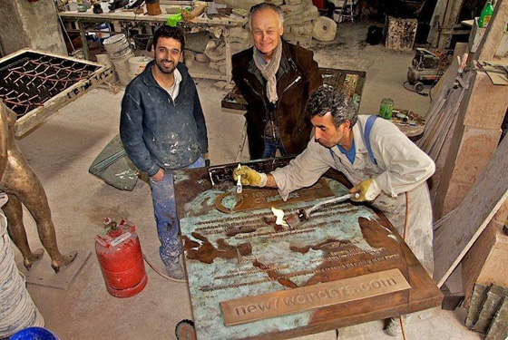 Bernard Weber, Founder-President of New7Wonders (centre), with Aslan Göktepe (left), as Hasan Göktepe (right) of the Kunstgießerei München applies the patina to the Puerto Princesa Underground River plaque.