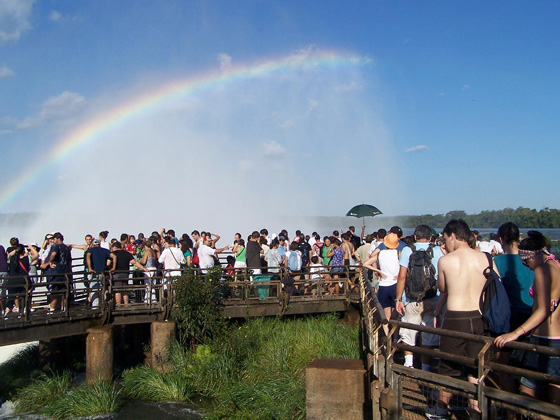 Rainbow over Iguazu Falls as visitors, fascinated by the sight and sound of the immense amounts of  falling water, marvel at this Wonder of Nature.
