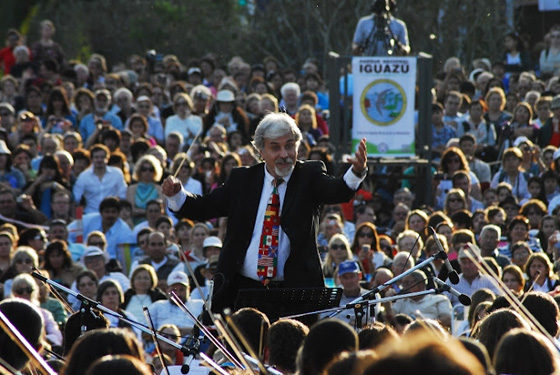 Gustavo Santaolalla conducting the youth international orchestra during the inauguration ceremonies in Puerto Iguazú, Argentina, marking the listing Iguazu Falls as one of the New7Wonders of Nature.