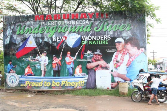 Celebratory poster at a junction in Puerto Princesa featuring Bernard Weber, Founder-President of New7Wonders, Mayor Edward Hagedorn of Puerto Princesa City and Jean-Paul de la Fuente, New7Wonders Director.