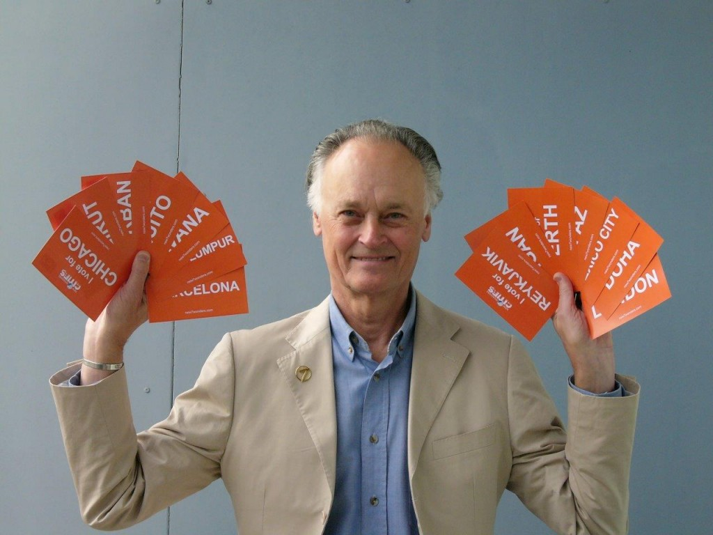 New7Wonders Founder-President Bernard Weber holds all the postcards.