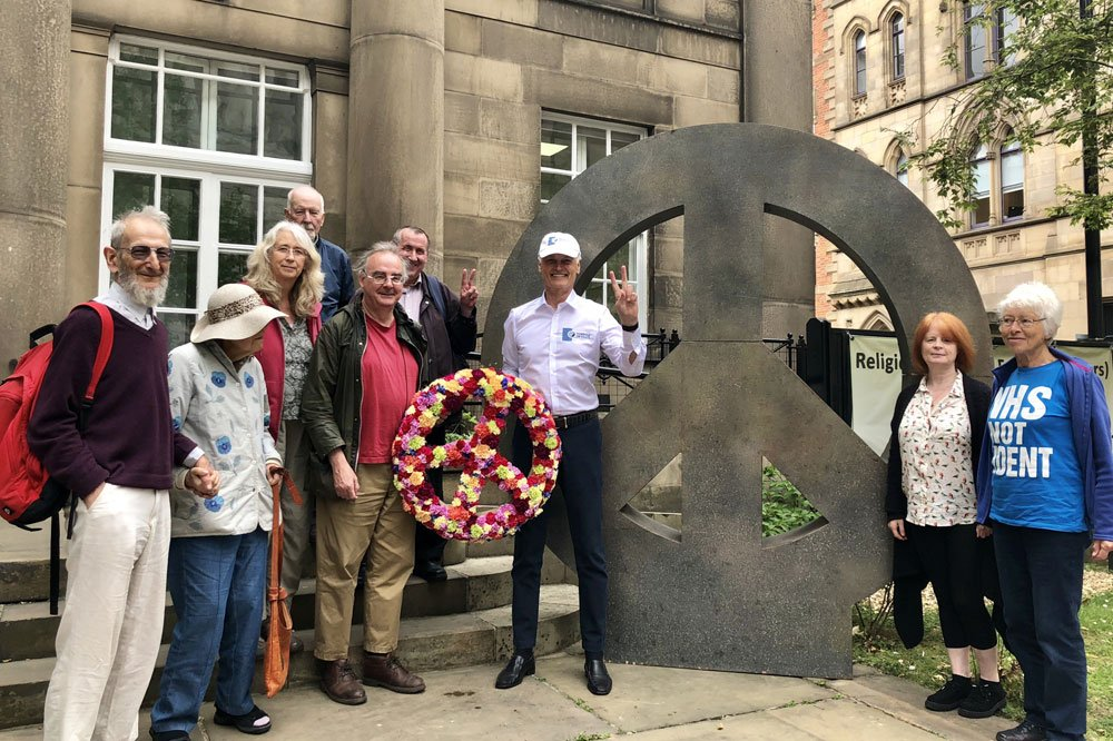 Bernard Weber, Founder of New7Wonders, celebrating the Campaign for Nuclear Disarmament (CND) symbol of peace, while presenting a flower version of the symbol to CND and the Quakers Elders at the Manchester Friends Meeting House.